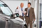 Mature salesman showing businessman car in showroom