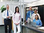 Five healthcare workers at reception desk, smiling, portrait