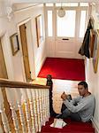 Man sitting at bottom of stairs reading postcard