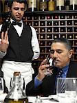 Senior businessman tasting wine in restaurant