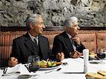 Two senior businessmen having meal in restaurant