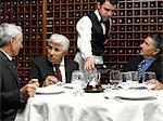 Waiter serving wine to businessmen in restaurant