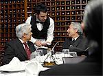 Waiter taking order from businessmen in restaurant