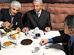 Three businessmen eating in restaurant, overhead view