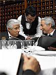 Waiter taking order from senior businessmen in restaurant