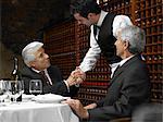 Waiter shaking senior businessman's hand in restaurant