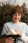 Boy (10-12) in garden holding top hat with rabbit smiling, portrait