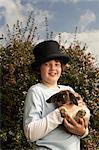 Boy (10-12) in garden wearing top hat with rabbit smiling, portrait
