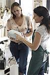 Female shop assistant assisting woman in interior design shop