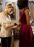 Fashion designer pinning female model's dress