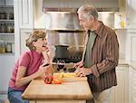 Senior couple in kitchen, man chopping vegetables, smiling