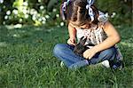 Girl (6-7) wearing hair bows, sitting on grass, holding rabbit