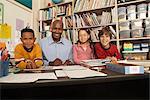 Teacher and three children (8-9) sitting at desk in classroom, portrait