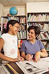 Teacher sitting at desk, smiling at girl (10-11)