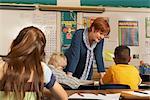Teacher leaning on desk, talking to children (8-9) in classroom