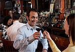 Couple toasting wineglasses at bar