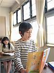Boy (6-7) reading textbook in school classroom