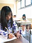 Girl (8-9) writing in school classroom