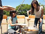 Three children (7-9) cooking in school playground