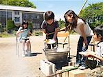Four children (5-9) cooking in school playground