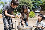Three children (5-9) cooking in school playground