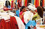 Salesgirl showing dress to customer in supermarket