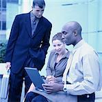 Businesspeople gathered around laptop (cross-processed)