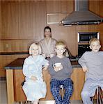Mother and three children (4-10) wearing pajamas in kitchen, portrait