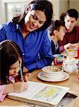 Parents helping children (6-8) with homework during breakfast