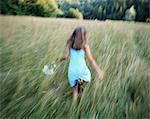 Girl (8-10) running through field, summer, rear view (panning)