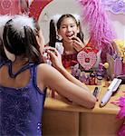 Girl (10-12) applying lipstick, looking in mirror, rear view