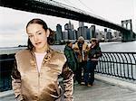 Teenage Girl Standing Apart From Group Under Manhattan Bridge in New York