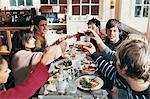 Friends Sitting in a Restaurant Raising their Glasses in Celebration