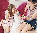 Two Teenage Girls Sitting Holding Mobile Phones