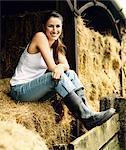 Woman Sitting on Hay Bales on a Farm