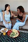 Women Sit Side by Side on a Sofa Eating a Healthy Breakfast