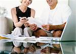 Couple Sitting on a Sofa Examining Their Invoices
