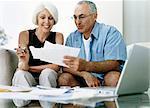 Senior Couple Sitting on a Sofa Examining Their Invoices