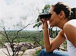 Woman Sitting on Car Bonnet Looking Through a Pair of Binoculars