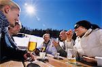Friends Enjoying a Drink at a Table at a Ski Resort