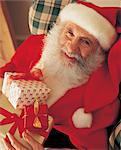 Portrait of Santa Claus Holding a Present