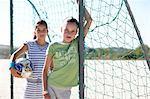 Two girls (9-12) in goal post, portrait