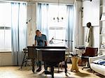 Mature man standing behind piano, writing