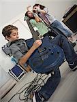 Boy (10-11) playing guitar, girls (6-7) singing in garage