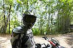 Mature biker on motocross in forest