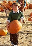 Boy (4-5) holding big pumpkin in patch
