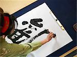 Woman writing calligraphy, high angle view