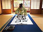 Japan, Tokyo, woman wearing kimono writing calligraphy on large piece of paper