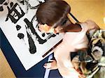 Japan, Tokyo, woman in kimono writing calligraphy, high angle view