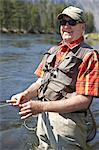 Portrait of senior man smiling while flyfishing
